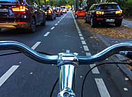 Ein Fahrradfahrer fährt auf einer eigenen Radfahrspur in der Bebelallee in Hamburg an einem Stau vorbei