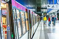 Ein U-Bahn-Zug vom Typ DT4 in der Haltestelle HafenCity Universität in Hamburg mit Menschen auf dem Bahnsteig