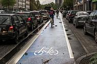 Fahrradfahrer radeln in der Grindelallee in Hamburg auf einer eigenen Radfahrspur an einem Stau vorbei