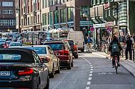 Eine Fahrradfahrerin fährt auf einem Schutzstreifen an einem Stau am Gänsemarkt in Hamburg vorbei
