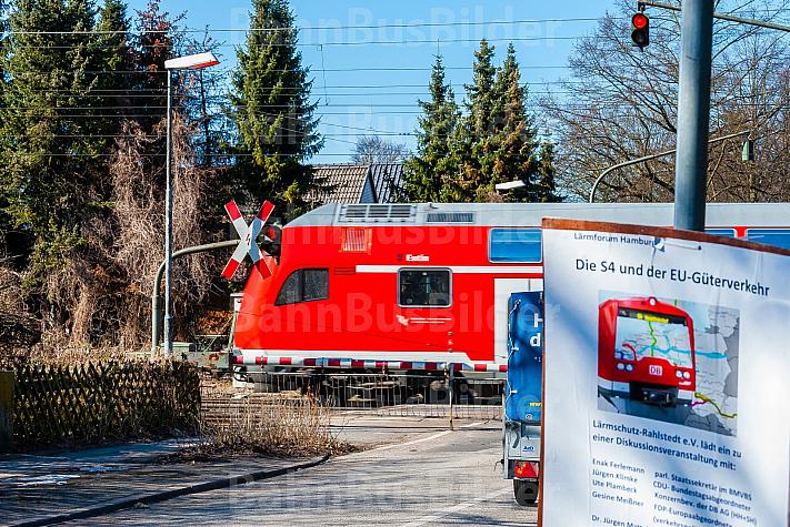 Regionalzug am Bahnübergang Claudiusstraße in Hamburg mit Plakat gegen die geplante S4