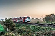 Ein Triebwagen der AKN fährt im herbstlichen Frühnebel über die Felder bei Bokholt in Schleswig-Holstein