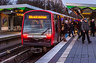 Menschen steigen in der Haltestelle Wandsbek-Gartenstadt in Hamburg aus einem endenden U-Bahn-Zug vom Typ DT5