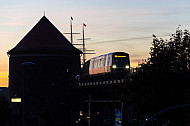 Ein U-Bahnzug der Baureihe DT5 bei Sonnenuntergang im Hamburger Hafen auf einem Viadukt