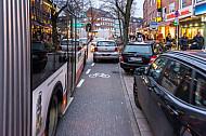 Mehrere Falschparker blockieren einen Fahrrad-Schutzstreifen in der Osterstraße in Hamburg. Radfahrer werden zwischen Linienbussen und parkenden Autos regelrecht eingezwängt.
