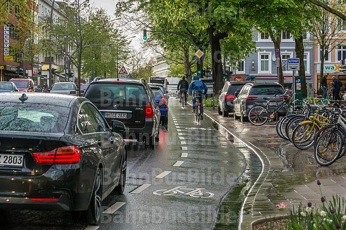 Fahrradfahrer fahren im Regen auf einer eigenen Fahrspur in der Osterstraße in Hamburg am Stau vorbei