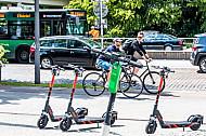 Mehrere E-Scooter verschiedener Leih-Anbieter stehen auf am Dammtor in Hamburg. Im Hintergrund zwei Fahrradfahrer.