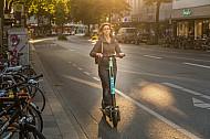 Eine E-Scooter-Fahrerin in der Abendsonne in der Osterstraße in Hamburg