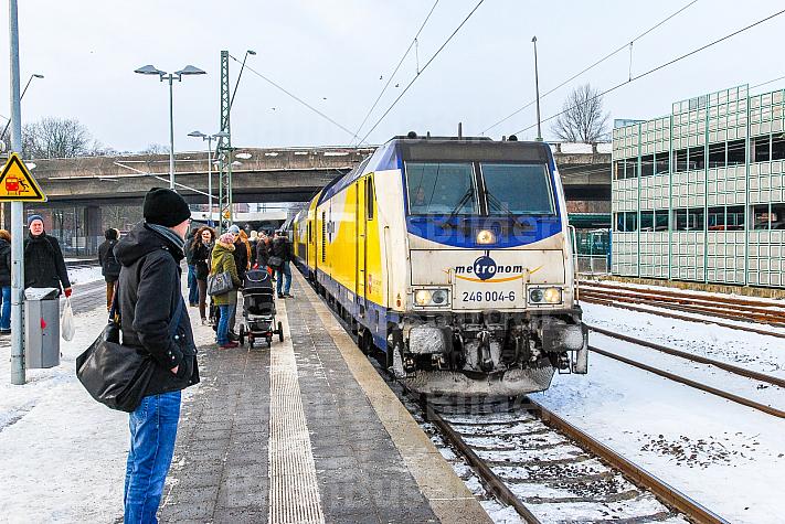 Menschen warten bei Schnee und Eis auf einen Metronom-Zug in Stade in Niedersachsen