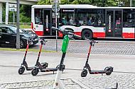 Mehrere E-Scooter verschiedener Leih-Anbieter stehen auf am Dammtor in Hamburg. Im Hintergrund ein Hochbahn-Bus.
