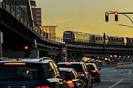 Eine Hamburger U-Bahn vom Typ DT5 fährt auf einem Viadukt im Hafen, während sich unten der Autoverkehr staut