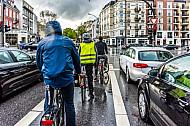 Fahrradfahrer stehen im Regen auf einer Radfahrspur an einer Ampel in Hamburg