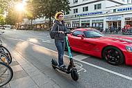 Eine E-Scooter-Fahrerin in der Abendsonne neben einem Auto in der Osterstraße in Hamburg