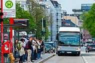 Menschen warten an der Universität in Hamburg auf einen Metrobus der Linie M5