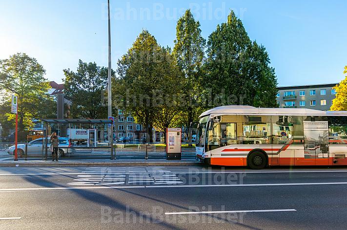 Eine Frau wartet an einer Haltestelle auf einen Bus