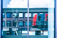 Ein U-Bahnzug vom Typ DT5 spiegelt sich in einem Bürogebäude in Hamburg