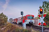 Ein Triebwagen der AKN im herbstlichen Frühnebel an einem Bahnübergang bei Sparrieshoop in Schleswig-Holstein