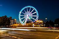 Autoverkehr vor dem Hamburger DOM mit Riesenrad im Abendlicht