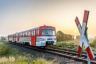 Ein Triebwagen der AKN fährt im herbstlichen Frühnebel und bei Sonnenaufgang über die Felder bei Bokholt in Schleswig-Holstein
