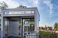 Ein Aufzug an der Haltestelle Legienstraße in Hamburg mit einem U-Bahn-Zug im Hintergrund