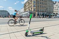 Ein E-Scooter steht am Jungfernstieg in Hamburg, im Hintergrund ein Fahrradfahrer