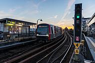 Ein U-Bahn-Zug vom Typ DT5 fährt bei Sonnenuntergang in die Haltestelle Baumwall im Hamburger Hafen ein