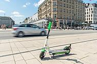 Ein E-Scooter steht am Jungfernstieg in Hamburg, im Hintergrund ein Auto