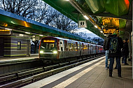 Menschen warten auf einem Bahnsteig in Wandsbek-Gartenstadt in Hamburg auf ihre U-Bahn, im Hintergrund endet ein Zug