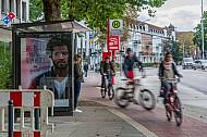 Ein Radweg mit Fahrradfahrern in Hamburg wird mitten durch eine Bushaltestelle geführt