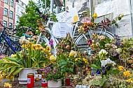 Blumen und ein weiß lackiertes so genanntes Ghostbike erinnern an eine 2018 getötete Fahrradfahrerin in Hamburg