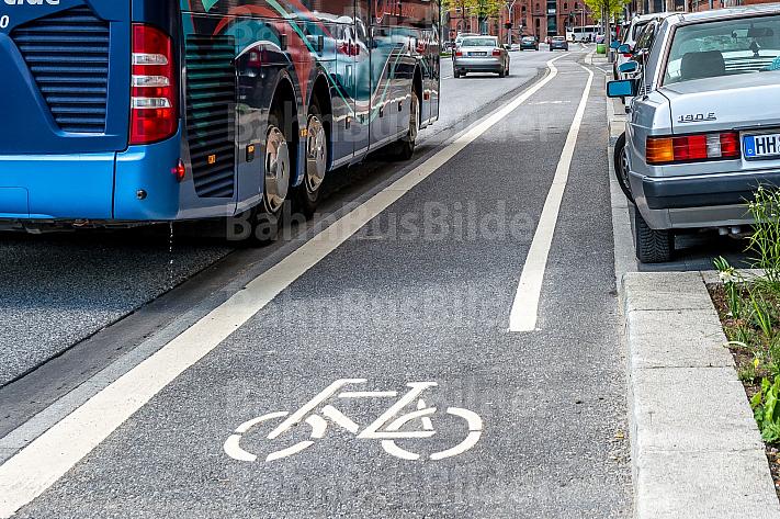 Eine vom Autoverkehr abgetrennte Fahrradspur in der Hamburger HafenCity zwischen parkenden Autos und Busverkehr