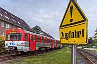 Ein Triebwagen der AKN fährt in den Bahnhof Barmstedt in Schleswig-Holstein ein - im Vordergrund warnt ein Schild vor Zugfahrten