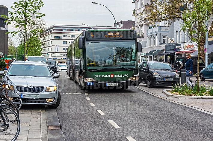 Ein Metrobus schlängelt sich zwischen Falschparkern durch die Osterstraße in Hamburg - die Fahrradspuren sind teilweise blockiert