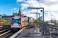 Ein U-Bahn-Zug der Baureihe DT3 am Bahnhof Landungsbrücken im Hamburger Hafen vor der Elbphilharmonie