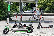 Mehrere E-Scooter verschiedener Leih-Anbieter stehen auf am Dammtor in Hamburg. Im Hintergrund eine Fahrradfahrerin