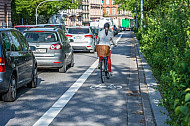 Eine Fahrradfahrerin fährt auf einem eigenen Radfahrstreifen an einem Stau in der Edmund-Siemers-Allee in Hamburg vorbei