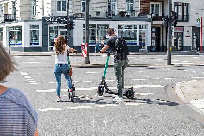 Zwei E-Scooter-Fahrer stehen an einer Ampel in Hamburg-EImsbüttel