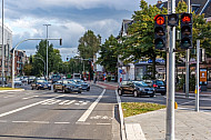 Eine Fahrradspur führt über eine vielbefahrene Kreuzung in Hamburg - eine eigene Fahrradampel zeigt Rotlicht
