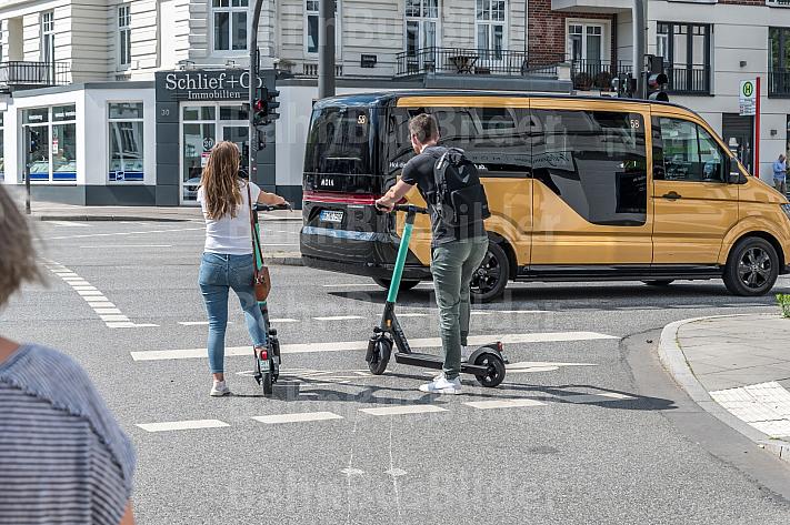 Intermodalität: Zwei E-Scooter-Fahrer stehen an einer Ampel in Hamburg-EImsbüttel. Im Hintergrund ein Bus des Ridesharing-Anbieters Moia