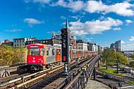 Ein U-Bahn-Zug der Baureihe DT3 auf der Viaduktstrecke im Hamburger Hafen vor der Elbphilharmonie