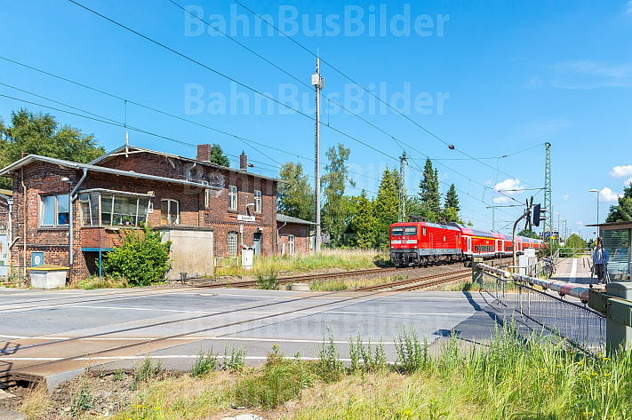 Regionalzug passiert Bahnübergang im Bahnhof Dauenhof in Schleswig-Holstein