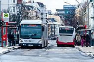 Menschen und Busse im Winter an einer Haltestelle in Hamburg