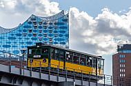 Ein historischer U-Bahnzug vom Typ T auf der Linie U3 vor der Elbphilharmonie in Hamburg