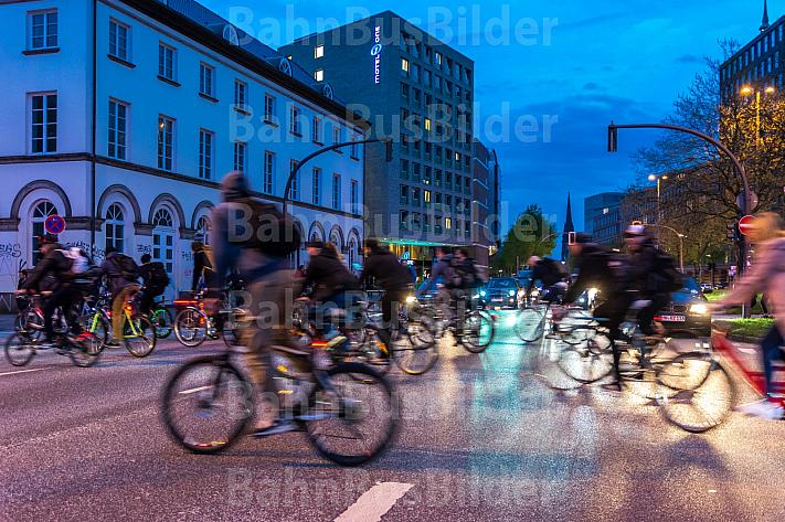 Zahlreiche Radfahrer überqueren im Abendlicht eine Hauptstraße in Hamburg