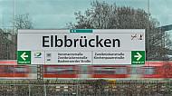Eine Haltestellenschild im U-Bahnhof Elbbrücken - im Hintergrund eine S-Bahn
