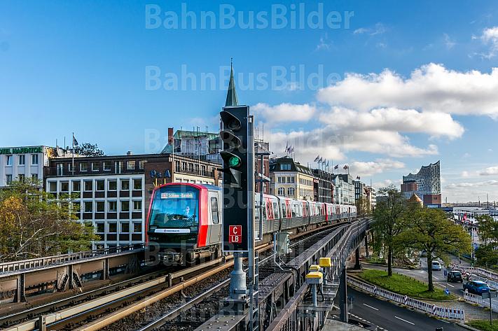 Ein U-Bahn-Zug der Baureihe DT5 auf der Viaduktstrecke im Hamburger Hafen vor der Elbphilharmonie