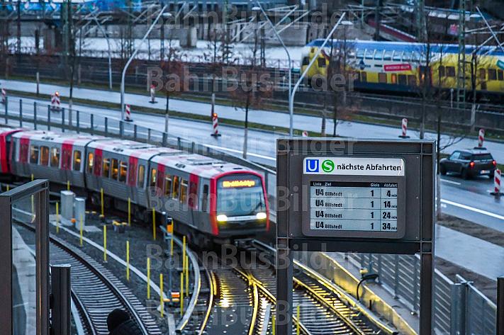 Eine U-Bahn der Linie U4 erreicht den Bahnhof Elbbrücken im Hamburger Hafen - im Hintergrund ein Metronom-Regionalzug