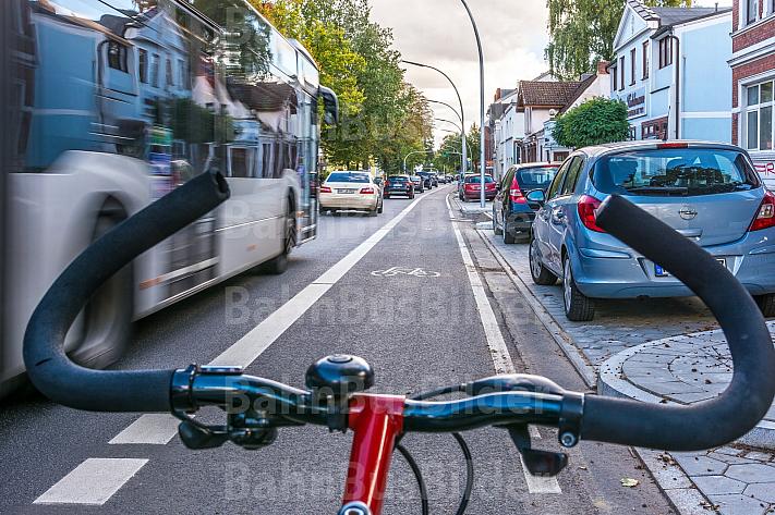 Ein Fahrradfahrer fährt auf einem vom Autoverkehr abgetrennten Radfahrstreifen in Hamburg - zwischen parkenden Autos und Busverkehr