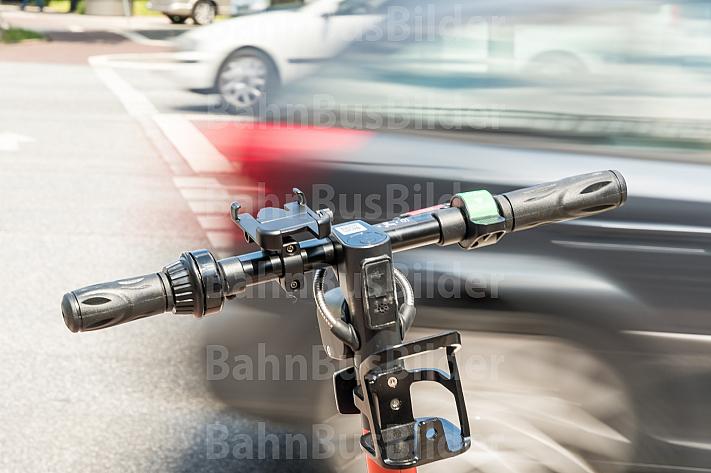 Ein E-Scooter steht an einer Ampel. Im Hintergrund kreuzt ein Auto.