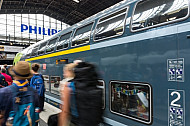Menschen laufen im Hamburger Hauptbahnhof vor einem Doppelstock-Zug der Deutschen Bahn